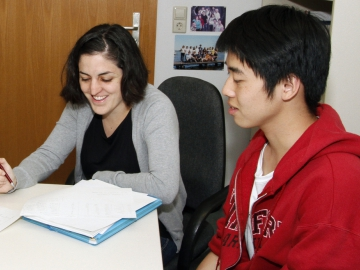A female and a male DESY-summer student sitting at a table with documents on it
