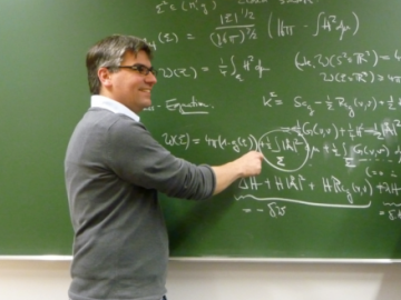 A male scientist from the AEI at a blackboard with mathematical formulas on it