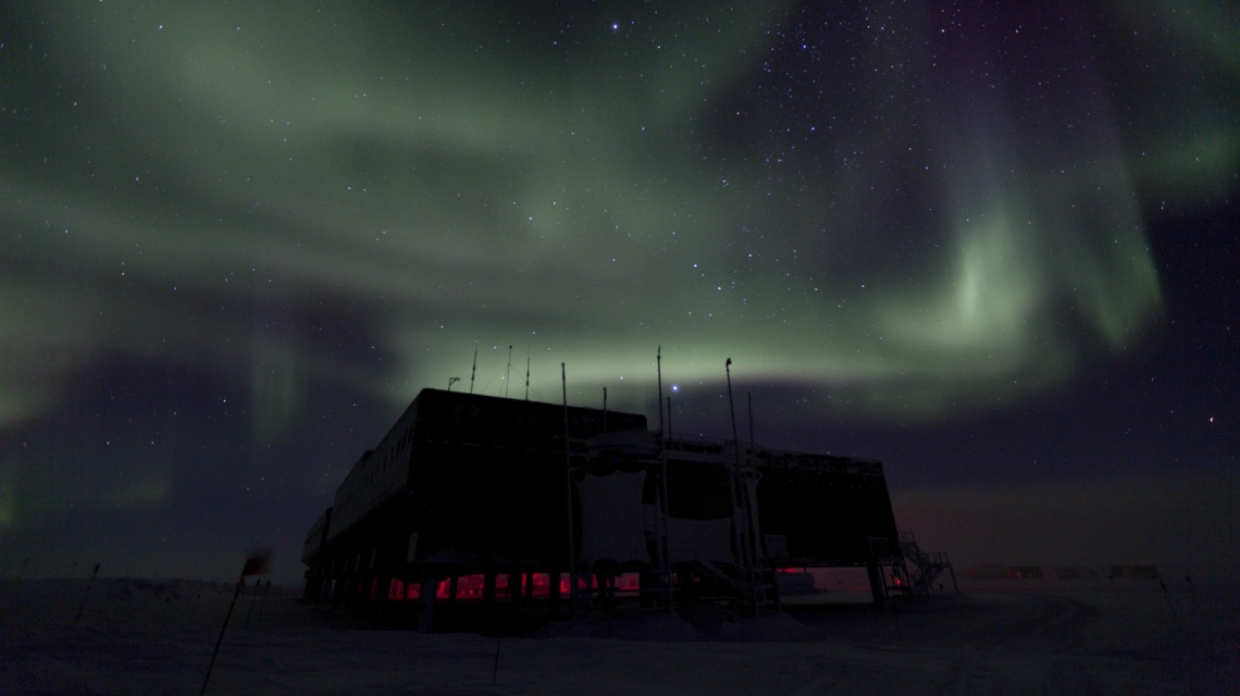 Polar lights over the IceCube laboratory during the polar night, with a starry sky in the background. (Credit: Freija Descamps/NSF, 2011)